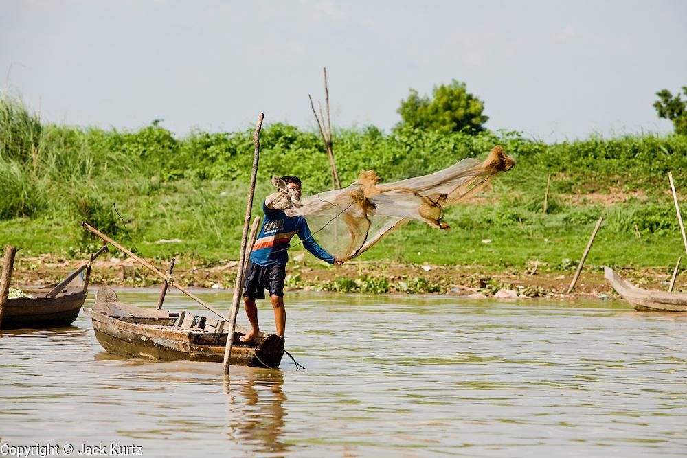 17 MARCH 2006 - KAMPONG CHHNANG, KAMPONG CHHNANG, CAMBODIA: A man throws a fishing net into the Tonle Sap River near the city of Kampong Chhnang in central Cambodia. PHOTO BY JACK KURTZ