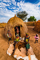 Nyangatom tribe women and children sit in front of their hut in their village, Omo Valley, Ethiopia.