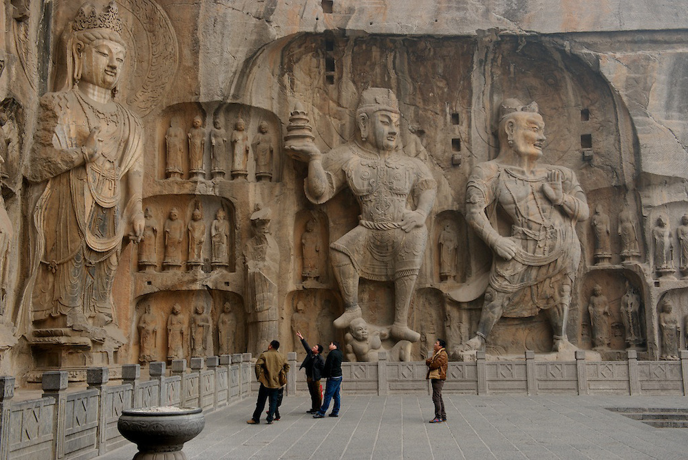"""The Longmen Grottoes (simplified Chinese: ????; traditional Chinese: ????; pinyin: lóngmén shíku?; lit. Dragon's Gate Grottoes) or Longmen Caves are one of the finest examples of Chinese Buddhist art. Housing tens of thousands of statues of Buddha and his disciples, they are located 12 kilometres (7.5 mi) south of present day Luòyáng in Hénán province, Peoples Republic of China. The images, many once painted, were carved into caves excavated from the limestone cliffs of the Xiangshan and Longmenshan mountains, running east and west. The Yi River flows northward between them and the area used to be called Yique (""""The Gate of the Yi River"""").[1][2][3] The alternative name of """"Dragon's Gate Grottoes"""" derives from the resemblance of the two hills that check the flow of the Yi River to the typical """"Chinese gate towers"""" that once marked the entrance to Luoyang from the south.[4].There are as many as 100,000 statues within the 1,400 caves, ranging from an 1 inch (25 mm) to 57 feet (17 m) in height. The area also contains nearly 2,500 stelae and inscriptions, whence the name ?Forest of Ancient Stelae"""", as well as over sixty Buddhist pagodas. Situated in a scenic natural environment, the caves were dug from a 1 kilometre (0.62 mi) stretch of cliff running along both banks of the river. 30% date from the Northern Wei Dynasty and 60% from the Tang, caves from other periods accounting for less than 10% of the total.[3] Starting with the Northern Wei Dynasty in 493 AD, patrons and donors included emperors, Wu Zetian of the Second Zhou Dynasty, members of the royal family, other rich families, generals, and religious groups.[1][5].In 2000 the site was inscribed upon the UNESCO World Heritage List as ?an outstanding manifestation of human artistic creativity,? for its perfection of an art form, and for its encapsulation of the cultural sophistication of Tang China.[2]"""