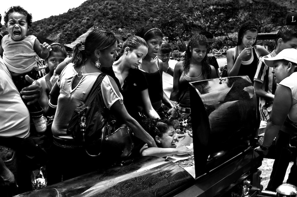 Family and friends mourn the death of Yanil Alexander Cemeño Figuera at his funeral in Caracas, Venezuela. Cemeño was fatally shot in Petare, and was his mother's fourth child to be murdered. Petare slum is one of the most violent areas of Caracas, Venezuela, reporting over a dozen homicides every weekend. According to the ngo, the Venezuelan Observatory of Violence (OVV), Caracas has one of the highest violent crime rates in the world, with two people murdered every hour, a homicide rate that has quadrupled over the eleven year presidency of Hugo Chávez. Equally disturbing is the level of impunity, corruption and incompetency in the Venezuelan judicial system. OVV reports that 91% of crimes go unsolved in Venezuela.