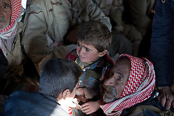© Licensed to London News Pictures. 11/12/2014. Sinjar Mountains, Iraq. An elderly Yazidi refugee holds on to a young relative inside an Iraqi Air Force Mi-17 helicopter as it evacuates both he and his family from Mount Sinjar.<br /> <br /> Although a well publicised exodus of Yazidi refugees took place from Mount Sinjar in August 2014 many still remain on top of the 75 km long ridge-line, with estimates varying from 2000-8000 people, after a corridor kept open by Syrian-Kurdish YPG fighters collapsed during an Islamic State offensive. The mountain is now surrounded on all sides with winter closing in, the only chance of escape or supply being by Iraqi Air Force helicopters. Photo credit: Matt Cetti-Roberts/LNP