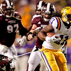 November 10, 2012; Baton Rouge, LA, USA; Mississippi State Bulldogs linebacker Benardrick McKinney (50) pulls on the towel of LSU Tigers running back Spencer Ware (11) on a run during the second quarter of a game at Tiger Stadium.  Mandatory Credit: Derick E. Hingle-US PRESSWIRE