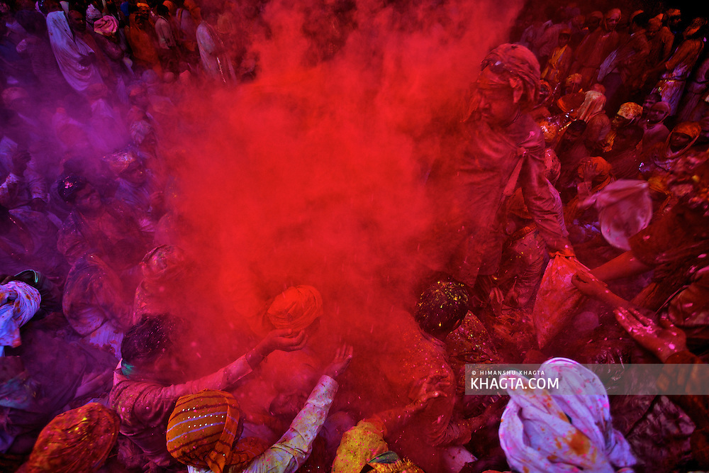 People surrounded in a cloud of red colored powered  asking for more colors in Barsana Village of Mathura while celebrating, 'the festival of colors', Holi.
