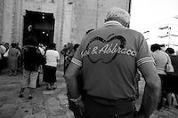 Un  fedele al quanto speciale data la sua maglietta griffata che attende l'uscita della statua della Madonna del Carmine protettrice di Mesagne in provincia di Brindisi.