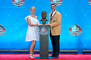 Aug 3, 2019; Canton, OH, USA; Kevin Mawae (right) poses with bust and presenter and wife Tracy Mawae during the Pro Football Hall of Fame Enshrinement at Tom Benson Hall of Fame Stadium. (Robin Alam/Image of Sport)