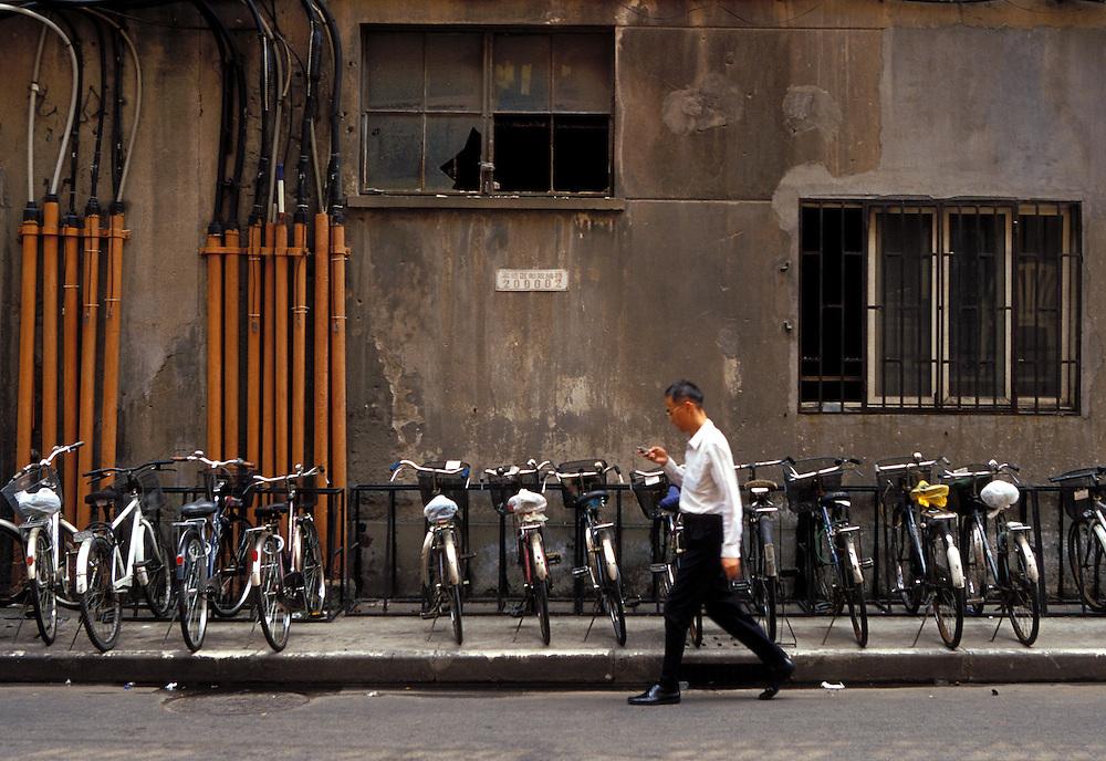 Un hombre camina por una calle de Shanghai mientras consulta su teléfono móvil.
