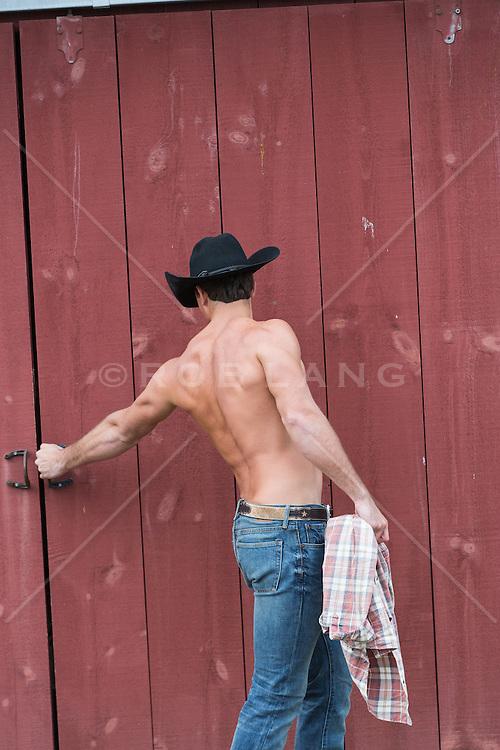 shirtless muscular cowboy opening a barn door