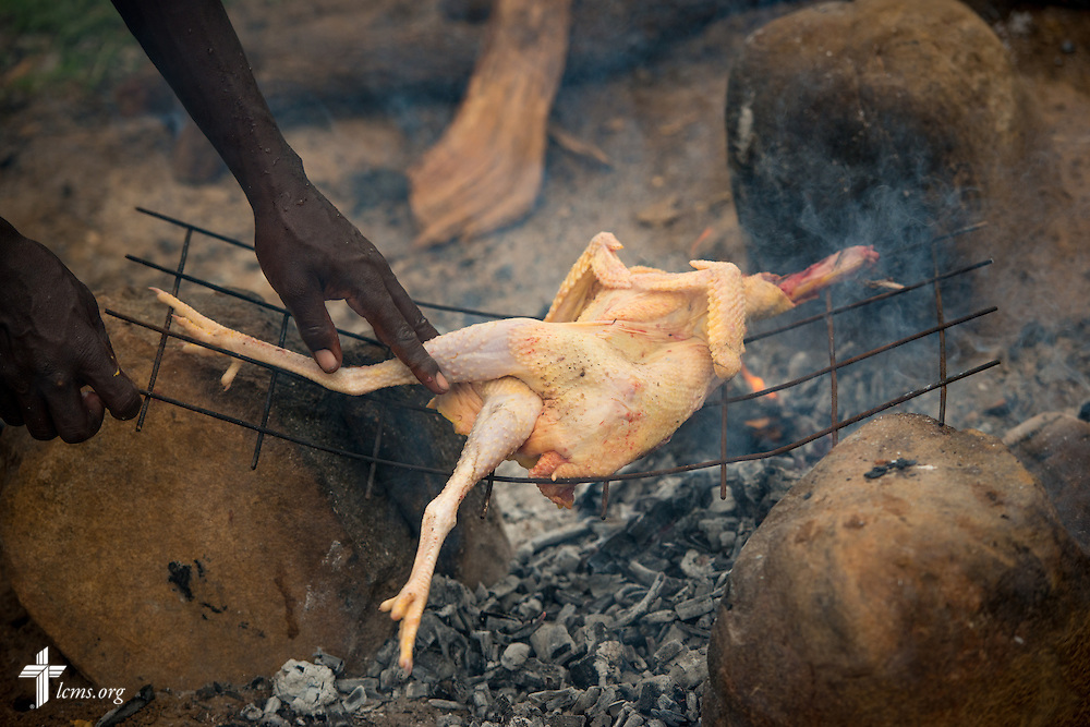 A chicken is roasted over a fire in preparation for dinner at the U-Dom ELCK (Evangelical Lutheran Church in Kenya) Project 24 site on Thursday, June 23, 2016, in Chepareria, Kenya.  LCMS Communications/Erik M. Lunsford