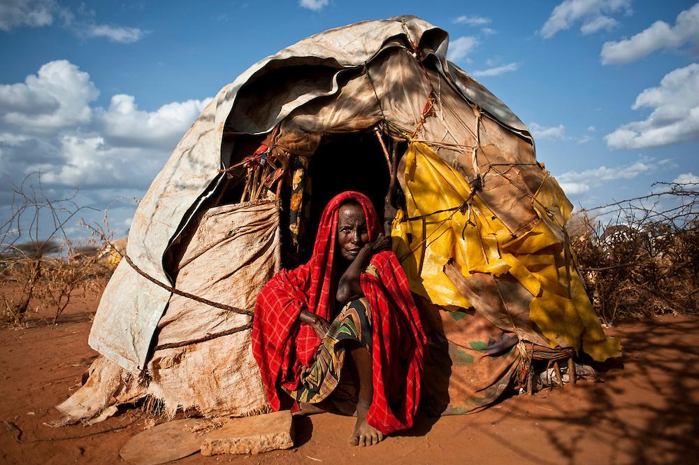 """Kenya, camp de réfugiés de Dadaab - Ifo 3. Hawo Aden, Salaghaley, 70 ans.                    """"Je ne me souviens même plus du goût de la viande"""". Hawo, 70 ans, est arrivée à Dadaab il y a cinq mois, elle est issue d'une famille de fermiers nomades. Ils ont laissé leurs dernières vaches en Somalie et sont partis dans la précipitation. Depuis qu'ils habitent le camp, ils cuisinent les rations que leur fournissent les ONG : chapatis, ugali, mais pour les légumes, ils doivent se débrouiller, en acheter sur un marché proche, ils en mangent donc extrêmement peu. Lorsquils élevaient leurs animaux, ils s'en tiraient plutôt bien. Les bêtes servaient de monnaie d'échange, surtout en cas de coup dur. Quand ils n'en ont plus eu, ils ont fui le pays pour trouver le minimum vital, soit 5 kilos de nourriture (huile, farines) pour 15 jours. Selon elle, ce n'est pas assez."""