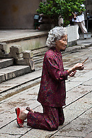 Women praying and making offerings of incense at Tin Hau Temple in Hong Kong