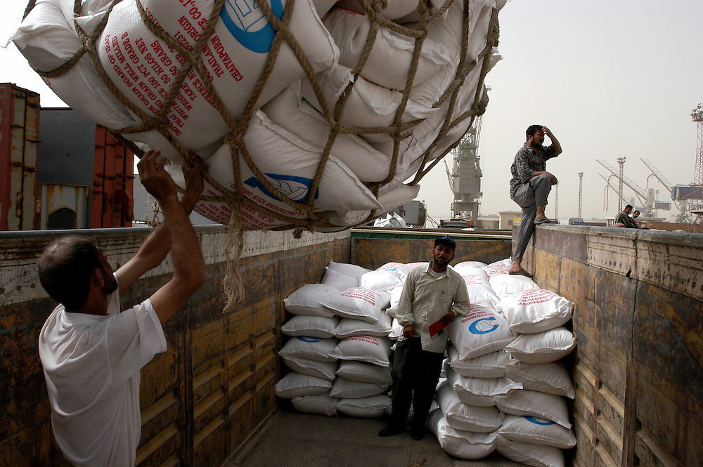 Dock workers from the town of Umm Qasr unload a shipment of humanitarian aid food stuffs at the port. Umm Qasr i s the first town in Iraq to be returned to an Iraqi administration. The reopening of the port to humanitarian shipments will provide much need jobs for the town..Umm Qasr, Iraq. 23 May 2003..Photo © J.B. Russell