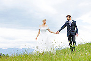 Bride and groom holding hands in the meadow