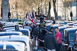 Whitehall, London, February 10th 2016. A taxi driver waves a Union Jack as an estimated 8,000 cabbies hold a go-slow in protest against what they say is unfair competition from minicab and Uber drivers who do not have to undergo the rigorous training and checks required for the licenced taxi trade. ///FOR LICENCING CONTACT: paul@pauldaveycreative.co.uk TEL:+44 (0) 7966 016 296 or +44 (0) 20 8969 6875. ©2015 Paul R Davey. All rights reserved.