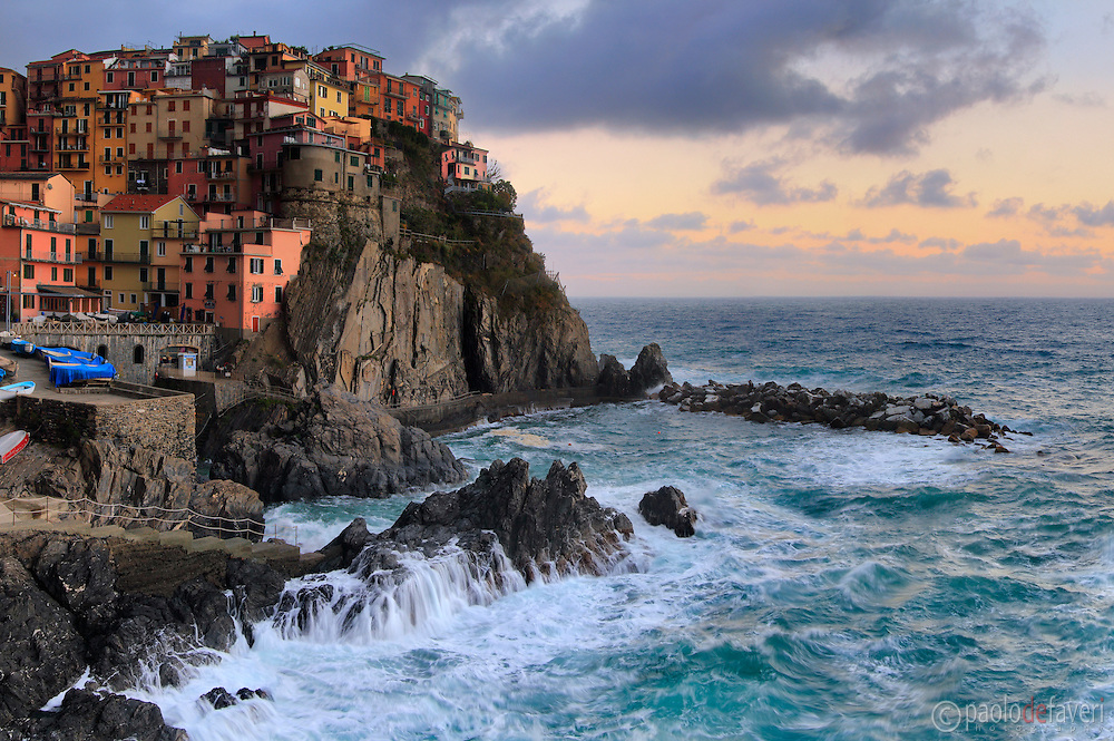 A view at dawn of the beautiful small fishermen village of Manarola, one of the five villages altogether known as Cinque Terre. Taken about 15 minutes before sunrise on a morning at the end of May, just after a storm with strong winds. This is stitched from five vertical frames.