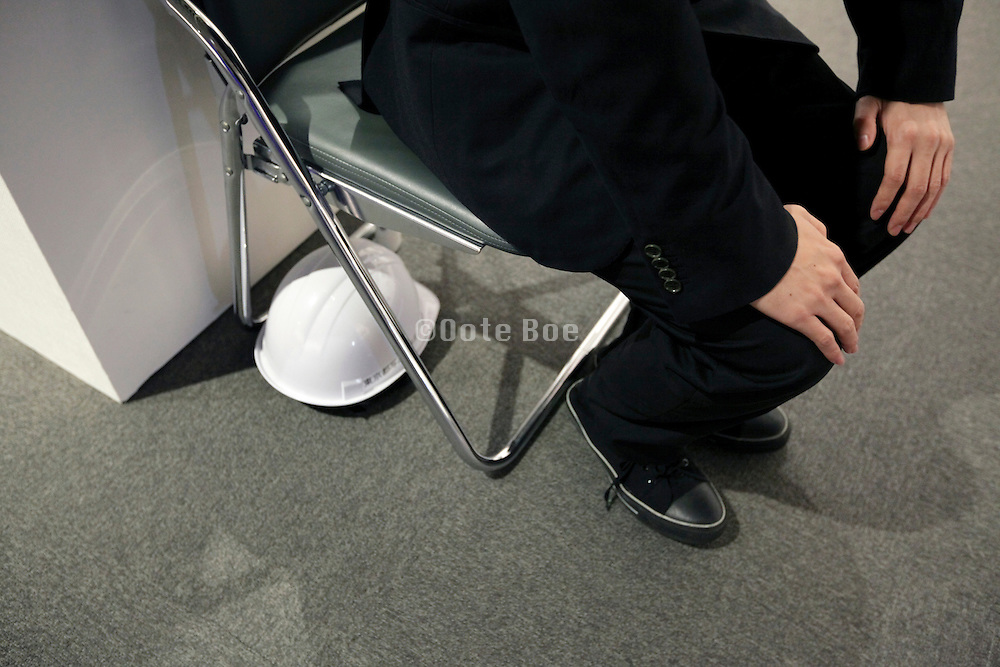 protective hard hat placed under a chair in public gallery Japan Tokyo