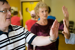 Woman Day Service Officer showing service users with learning disabilities a dance movement,