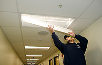 Facilities Director, Bill Caruso, snaps a fixture in place on the retrofit LED 2x4 light panels at Laconia Middle School Tuesday morning.  (Karen Bobotas/for the Laconia Daily Sun)