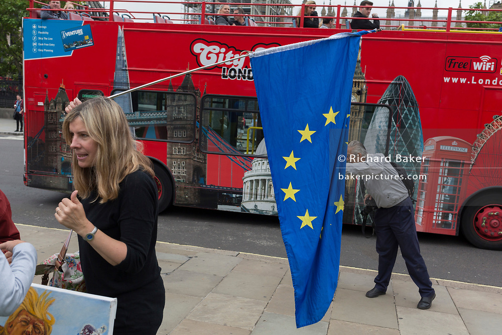Pro-Europe protesters display the EU flag in front of Parliament and a passing tour bus after the last chimes of Big Ben were controversially silenced by the repair project that is scheduled to be completed by 2021, on 21st August 2017, in London, England.