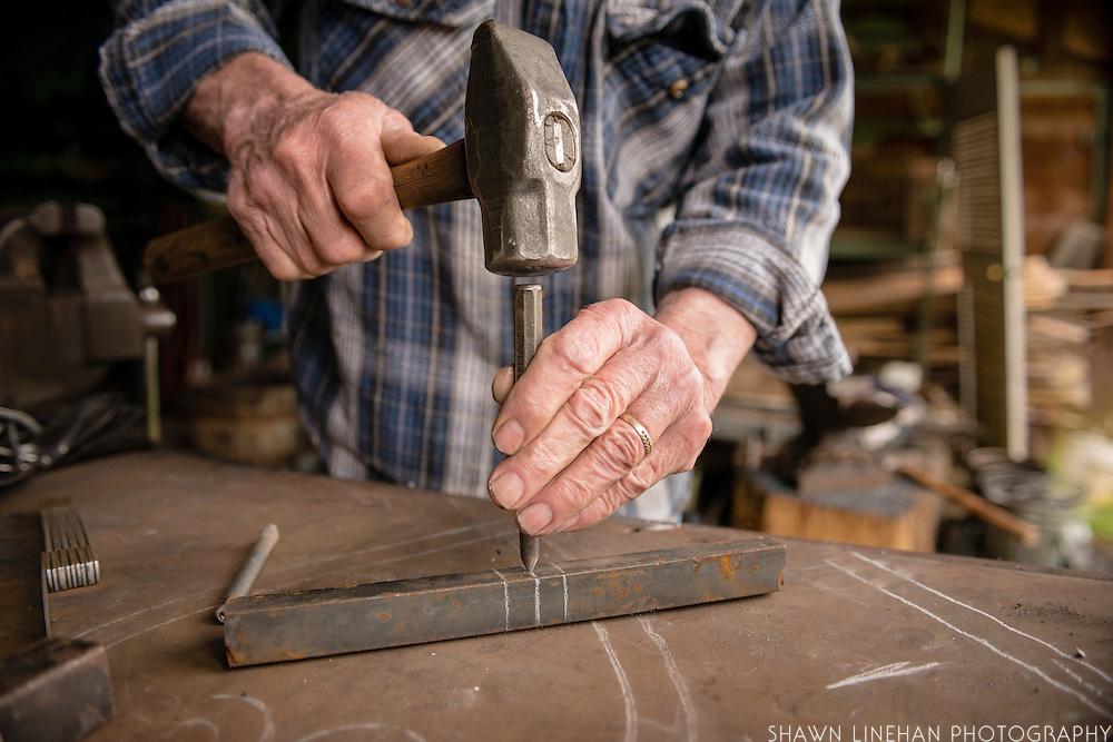 Hands hammer a big  nail into a metal rod