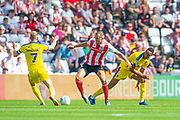 Charlie Wyke (#9) of Sunderland AFC cuts between Scott Wagstaff (#7) of AFC Wimbledon and Terell Thomas (#6) of AFC Wimbledon during the EFL Sky Bet League 1 match between Sunderland and AFC Wimbledon at the Stadium Of Light, Sunderland, England on 24 August 2019.