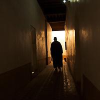 Man walking at of Ben Youssef Medersa's long corridors