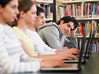 Students sitting in row using laptops in library