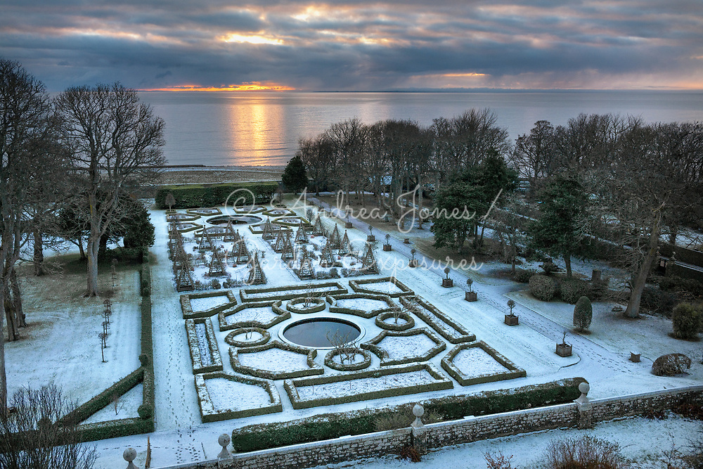 Snow covering the West Parterre as the sun rises over the North Sea<br /> <br /> Dunrobin Castle Sutherland, Scotland