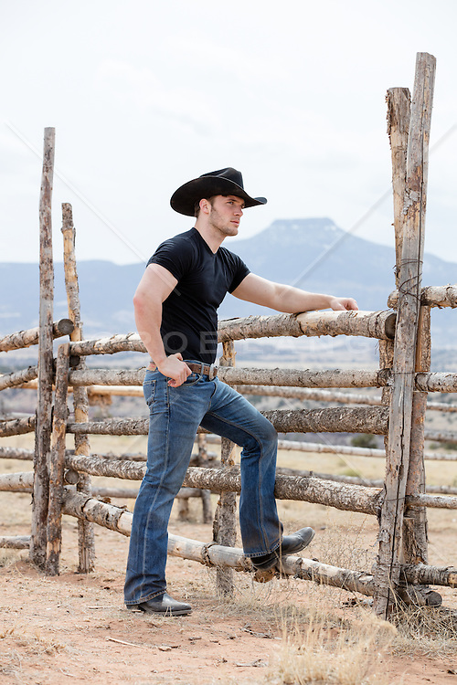 cowboy leaning on a rustic wooden fence outdoors overlooking a mountain range