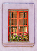 Spain, Barcelona. Window with flowers.