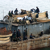 NORTHERN CHINA-APRIL 25:  North Korean workers transport boats on the Yalu river that divides China and North Korea on April 24, 2004 in Dandong, China. On April 22, 2004 at least 154 people died and more than 1300 were injured following a train explosion in Ryonchon, a North Korean town 20 km from the Dandong border. China has vowed to give North Korea $1.21 million worth of medical supplies, tents and food to help it cope with the disaster