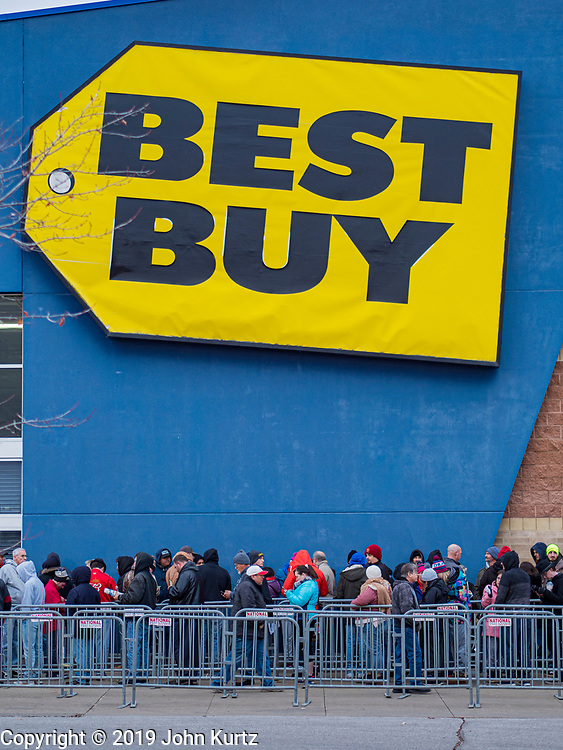 """28 NOVEMBER 2019 - ANKENY, IOWA: Holiday shoppers line up in front of the Best Buy in Ankeny Thursday evening. """"Black Friday"""" is the unofficial start of the Christmas holiday shopping season and has traditionally thought to be one of the busiest shopping days of the year. Brick and mortar retailers, like Best Buy, are facing increased pressure from online retailers this year. Many retailers have started opening on Thanksgiving Day. Many Best Buy stores across the country opened at 5PM on Thanksgiving to attract shoppers with early """"Black Friday"""" specials.           PHOTO BY JACK KURTZ"""