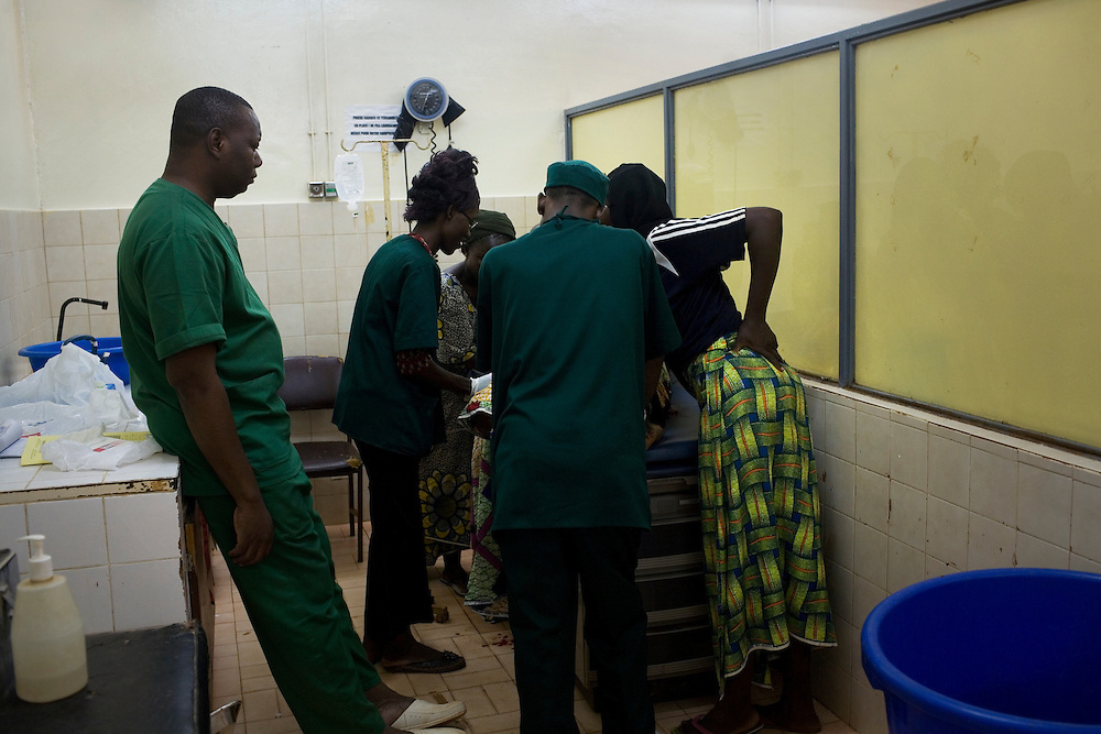 Staff suround and examine Alima while she has seizures and continue to bleed. They diagnose eclampsia and the added complication that her blood is not clotting, the only  way to save her life is an emergency caesarian. Hospital Yalgado, Ouagadougou, Burkina Faso