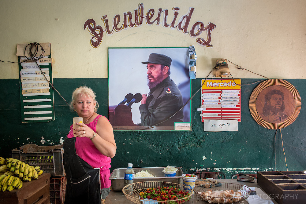 A saleswoman has a drink in a break of a working day at a fruit and vegetable shop in Havana. Pictures of Fidel Castro and Che Guevara are on the wall. Cuba, 2015.