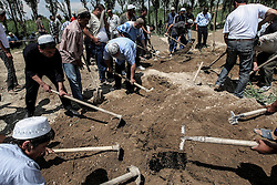 Uzbek men bury a family with four daughters, killed and burned during the ethnic clashes in Osh, Kyrgyzstan 16 June 2010. One hunded and eighty seven people were killed and 1918 wounded during the ethnic clashes in Kyrgyzstan during past days.