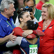 Gymnastics - Olympics: Day 6 Simone Biles #391 of the United States and Alexandra Raisman #395 of the United States embrace as the final result comes through confirming gold and silver medal for the pair as their coaches Aimee Boorman and Mihai Brestyan  congratulate each other during the Artistic Gymnastics Women's Individual All-Around Final at the Rio Olympic Arena on August 11, 2016 in Rio de Janeiro, Brazil. (Photo by Tim Clayton/Corbis via Getty Images)