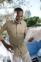 Portrait of senior man holding map