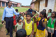 Mr Sarujit, 40, (left) project coordinator of the local charity Jago Foundation, whose Karate project is being sponsored by Unicef, is walking among children in Algunda village, pop. 1000, Giridih District, rural Jharkhand, India.