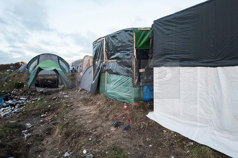 "© Licensed to London News Pictures. 12/01/2016. London, UK. Pink markings on the ground and on buildings to lay out the location of a new ""buffer zone at the migrant camp in Calais referred to as the Jungle. French authorities have announced they are creating a 100m buffer zone between the edge of the 'Jungle' camp and the motorway. Aid agencies estimate this will displace around 1700 people, including 300 women and 60 children. Photo credit: Rob Pinney/LNP"