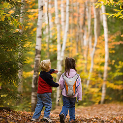 A young brother and sister (ages 4 and 6) hike on the Lincoln Woods Trail in New Hampshire's White Mountain National Forest.