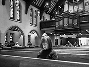 """15 MARCH 2020 - DES MOINES, IOWA: A woman sits by herself during Sunday services in St. John's Lutheran Church in Des Moines. Attendance at St. John's was about ⅔ below normal for a Lenten Sunday. Most churches in the Des Moines area canceled their Sunday services or switched to an online service this week. Those churches that conducted Sunday services imposed """"social distancing"""" guidelines, including no physical contact, and had significantly lower attendance. The Governor of Iowa announced Saturday night that the Coronavirus in Iowa had entered the """"community spread"""" phase when a person in Dallas County, in the Des Moines metropolitan area, tested positive for Coronavirus. This is the first reported case in the Des Moines area. As of Sunday morning, Iowa was reporting 18 people tested positive for Coronavirus.          PHOTO BY JACK KURTZ"""