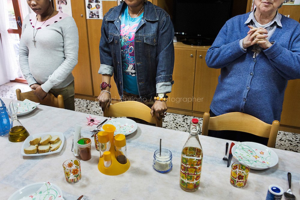 CASERTA, ITALY - 25 FEBRUARY 2015: (L-R) Two Nigerian ex-sex workers and an Ursuline sister pray before lunch at Casa Rut, a shelter for abused young immigrant women in Caserta, Italy, on February 25th 2015.<br /> <br /> Casa Rut was founded in 1995 and it is promoted and managed by the Ursuline Sisters of the Sacred Heart of Mary of Breganze (Vicenza, Italy).  Casa Rut's goal is to provide young immigrant women a familiar environment where  they are helped to protect and free themselves, and to undertake a common path aiming to the integration in Italy's society.