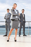 Full length portrait of confident businesswoman standing with coworkers on terrace against sky