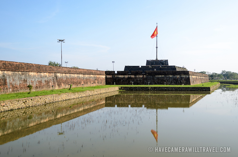 The citadel and moat at the Imperial City in Hue, Vietnam. A self-enclosed and fortified palace, the complex includes the Purple Forbidden City, which was the inner sanctum of the imperial household, as well as temples, courtyards, gardens, and other buildings. Much of the Imperial City was damaged or destroyed during the Vietnam War. It is now designated as a UNESCO World Heritage site.