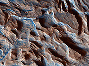 Becquerel Crater is one of several impact craters in Arabia Terra, on Mars, that have light-toned layered deposits along the crater floor. The light-toned deposits are particularly striking to look at in this HiRISE image because they are stacked together to produce a thick sequence of layered beds. The layers appear to be only a few meters thick and show little variations in thickness. Some of the layering in the image appears dark, probably due to deposition of basalt sand along flatter surfaces rather than any compositional variations in the layer beds themselves. Faults can also be seen displacing portions of the layered beds. The surface of the light-toned deposit is not smooth but instead appears disrupted into polygonal cracks and blocks.