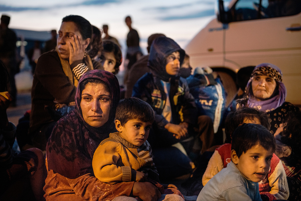 Syrian Kurdish people get into bus after crossing the border between Syria and Turkey after several mortars hit both side in the southeastern town of Suruc, in the Sanliurfa province. Tens of thousands of Syrian Kurds flooded into Turkey fleeing an onslaught by the Islamic State (IS) group that prompted an appeal for international intervention. Some refugees now want to return to protect their homes and join the fight against Islamic State group militants.