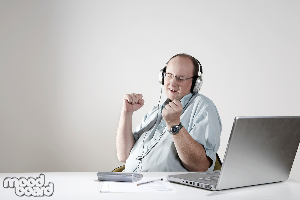 Businessman with earphones relaxing at desk