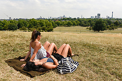© Licensed to London News Pictures. 25/07/2018. LONDON, UK.  University students, Lyn Tan and Rachelle Tan, enjoy the weather on Primrose Hill amidst parched grass and hot conditions.  The forecast is for temperatures to rise to 35C by the end of the week.  Photo credit: Stephen Chung/LNP