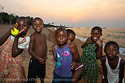 Children play at sunset on the shores of Likoma Island, Lake Malawi, Malawi.