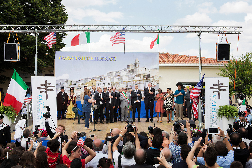 GRASSANO, ITALY - 24 JULY 2014: Mayor of New York Bill de Blasio and his family (center-left), together with Mayor of Grassano Francesco Sanseverino and local government officials (center-right), listen to the American national anthem on stage in Grassano, Mr de Blasio's ancestral home town in Italy, on July 24th 2014.<br /> <br /> New York City Mayor Bill de Blasio arrived in Italy with his family Sunday morning for an 8-day summer vacation that includes meetings with government officials and sightseeing in his ancestral homeland.