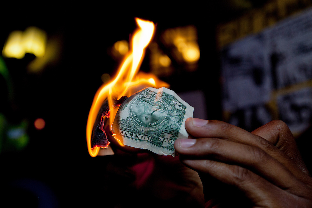 An Occupy LA demonstrator sets fire to a dollar bill in a show of protest in front of the Federal Reserve bank in Los Angeles, Calif. on Tuesday, November 22, 2011. (Photo by Gabriel Romero ©2011)